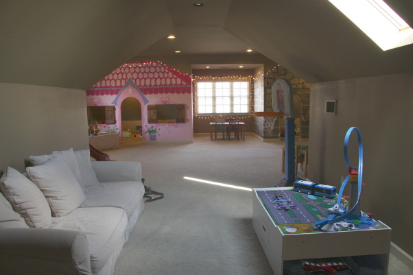 The Ultimate Playroom!, This space is our children's playroom. This playroom is for both boys and girls - and even fun-loving adults!, Standing in front of the tv room and taking a photo of the playhouse side of the playroom. , Other Spaces Design