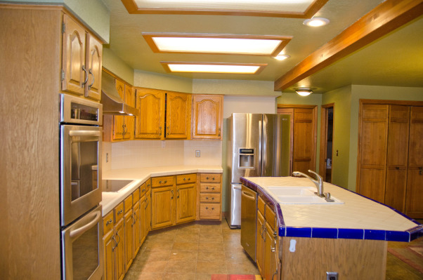 Kitchen Before and After, old country cabinets and tile counters, Golden yellow cabinets and dated light fixtures. The  island was tiled and had an awkward angle. The counter space was limited.      , Kitchens Design