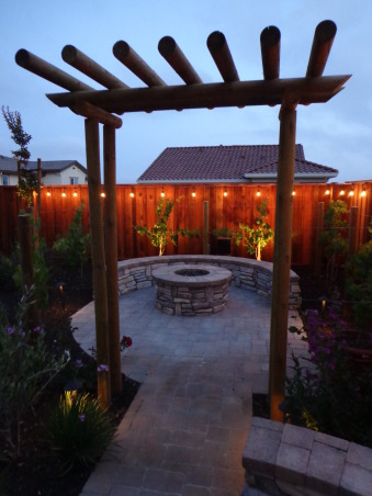 Outdoor Bar, Fire Pit, and Mini Vineyard, This is my husband's dream backyard.  It includes an outdoor bar & cooking area, BBQ, fire pit, & mini vineyard.  One day we will have patio furniture and chairs by the fire pit, but one thing at a time!, fire pit and arbor walkway           , Yards Design