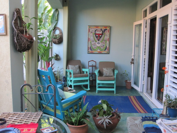 Patio in the Caribbean, Eclectic patio, with different finds that have been repainted.  Color theme is blues and greens.The flooring is colored concrete  using cement pigments. The pergola is covered with clear zinc to allow the light in, which at night time is lighted with solar power lights. There are green outdoor curtains.  A place to just relax., Outdoor patio in blues and greens. , Patios & Decks Design