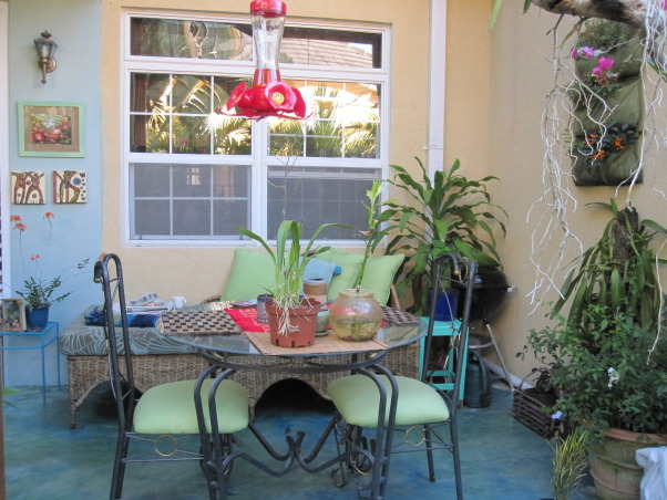 Patio in the Caribbean, Eclectic patio, with different finds that have been repainted.  Color theme is blues and greens.The flooring is colored concrete  using cement pigments. The pergola is covered with clear zinc to allow the light in, which at night time is lighted with solar power lights. There are green outdoor curtains.  A place to just relax., Hummingbird feeder , Patios & Decks Design