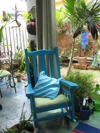 Patio in the Caribbean, Eclectic patio, with different finds that have been repainted.  Color theme is blues and greens.The flooring is colored concrete  using cement pigments. The pergola is covered with clear zinc to allow the light in, which at night time is lighted with solar power lights. There are green outdoor curtains.  A place to just relax., Refurbish rocking chair. , Patios & Decks Design