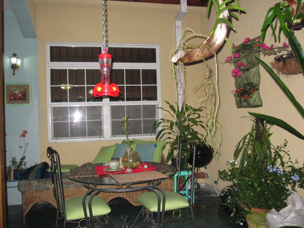 Patio in the Caribbean, Eclectic patio, with different finds that have been repainted.  Color theme is blues and greens.The flooring is colored concrete  using cement pigments. The pergola is covered with clear zinc to allow the light in, which at night time is lighted with solar power lights. There are green outdoor curtains.  A place to just relax., At night , Patios & Decks Design
