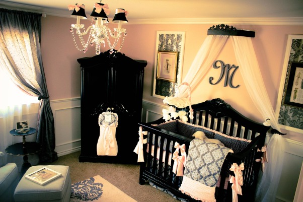 "Emmy's Parisian Chic Nursery, When my husband and I found out we were having a little girl, my wheels immediately started spinning and construction began!  I have always loved wainscot, so that was the first DIY project my husband tackled. I maximized space by setting the armoire caddy-corner with a changing station to the left and the crib directly on the opposing wall.  The glider and ottoman is also caddy corner next to the changing station. I found an antique mahogany two-tier table with scallop edging from Craigslist -$50- and refinished it in a black pearl stain with gold etching and tulip flowers with the letter M for Baby Morgan. The picture-in-picture was a design inspiration that my mom found in an interior decor magazine. We replicated the idea, wallpapering each of the inside panels bordered with molding, and placed vintage pictures that have been with my family for several years. On the 'changing station' wall, the other two picture-in-pictures have wired vintage figures of a manikin silhouette and Eiffel tower for that Parisian flare. My mother-in-law made all the bedding, drapery, and diaper hanging sack from fabric we picked out a local fabric warehouse in Buena Park, CA.  The crib cornice and curtain tie backs were a great find at the Princess Canopy Shop on Etsy. They are stained in black pearl with brass/gold etching.  My husband designed the M monogram and had it carved for under $40.  I bought the hanging chandelier on closeout with black shades and matching pink bows were tied using the leftover pink satin bedding fabric. The furniture was purchased locally and the lamp was purchased on clearance at Tuesday Morning -$50-. I shopped around for the rug after finding that on an interior design website, I bought it for 50% less than retail from BoldRugs.com after they price matched another competitors price. The crib mobile was purchased on target.com., All bedding was made by my mother-in-law, including the diaper hanging sack. My husband designed the ""M"" monogram above the crib and had it carved for under $40. The cornice and tie backs are from Princess Canopy Shop on Etsy. The rug is from boldrugs.com.   , Nurseries Design"