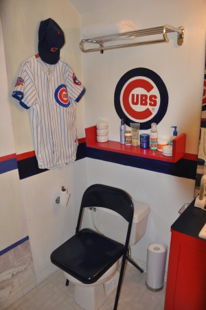 Boys Baseball bathroom , We're Cubs fans... condolences PLEASE! Once a Cubs Fan always a Cubs fan. The tradition of dying of old age waiting for a Cubs WS continues. In the interim we  turned our son's  bathroom into the Cubs locker room. Ernie Bank's locker is just across from our son's..talk abotu fantasy ball.  The mural  is complete with shoes and socks strewn so that  our son's own dirty socks on the floor won't stand out so much.   The design  was intended to visually extend what is a small bathroom.  , Toilet as a seat in the Cubs locker room , Boys' Rooms Design