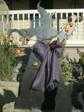 Outdoor Halloween Decor 2012, Here is a look at my outdoor Halloween decorations for the season. I made the witch and black cats myself. It's a simple look but still very spooky, especially at night. Hope you like it!, A close-up of the witch, accented with pumpkin lights and a big purple bow. I used purple mesh ribbon to make the bow., Home Exterior Design