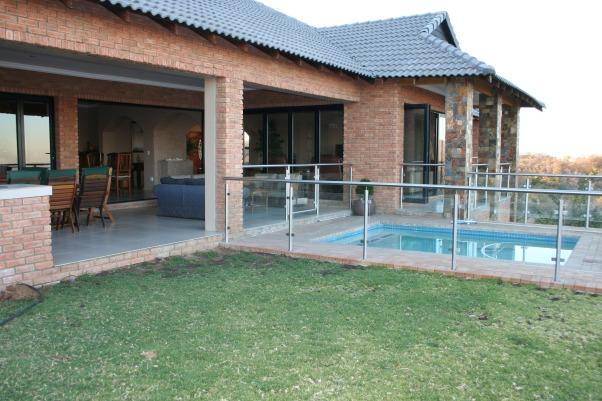 Our gorgeous patio  - where we spend most of our free time, Double patio with swimming pool and grassed area. Built in coal barbeque, next to a pizza oven. Work space with sink., Grassed play area and swimming pool, leading onto the double patio, with wicker suite and wooden dining table. Built in barbeque and pizza oven. Work area and sink., Patios & Decks Design