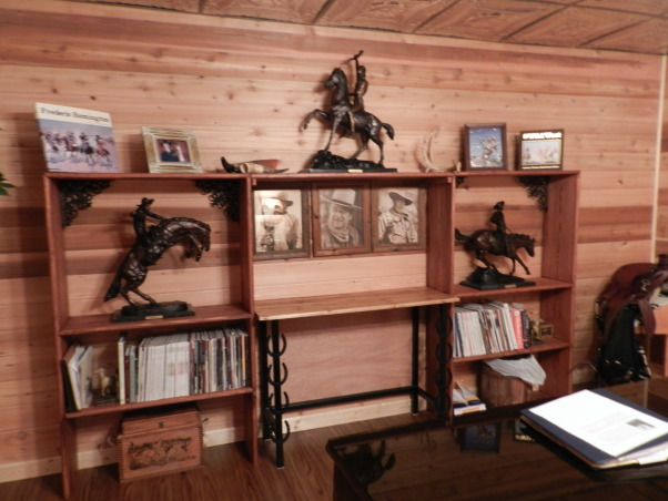 Western Basement Home Office, This is a basement space where I created my husband's home office.  It has a suspended tin ceiling, horse tapestry from Italy, Antiques, Family Heirlooms, Frederic Remington sculptures, handmade bookcase, wagonwheel chandelier, Western Style because my husband is a Farrier., Handmade bookshelf to house brass Frederic Remington sculptures, computer table specially made for space with horseshoes and metal legs.  And, no man's office should be without John Wayne!, Basements Design