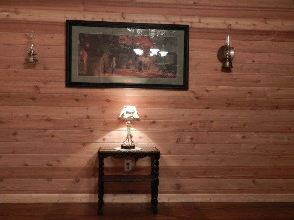 Western Basement Home Office, This is a basement space where I created my husband's home office.  It has a suspended tin ceiling, horse tapestry from Italy, Antiques, Family Heirlooms, Frederic Remington sculptures, handmade bookcase, wagonwheel chandelier, Western Style because my husband is a Farrier., Tongue and Groove Cedar on the walls, antique oil lanterns on the wall, Basements Design