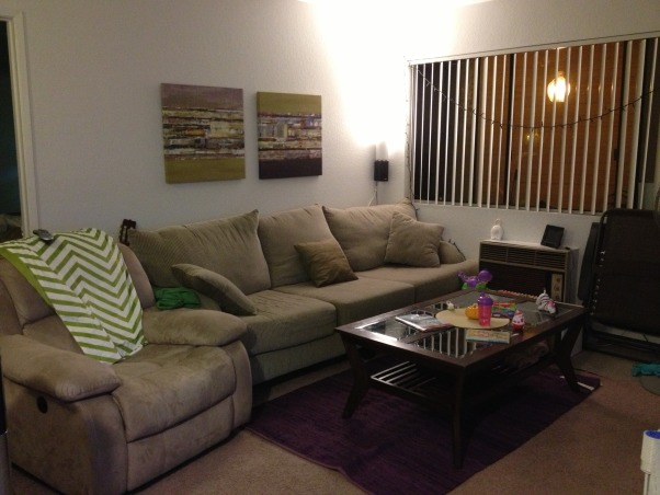 Need help with accent colors!, This is my small apartment living room. Unfortunately I can't paint it so I'm trying to accessorize with dark purple and green. I just got the purple rug, is it to much? I'm thinking of returning it. Plus, what could I add to this back wall? It feels so naked even with the two paintings. All help is appreciated and needed!!, Living Rooms Design