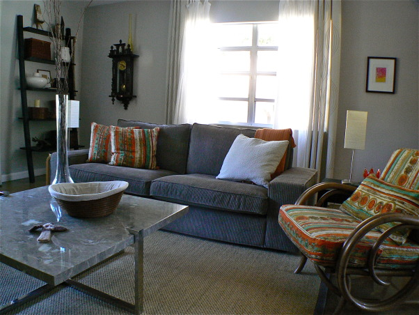 Change for the seasons, 15 x 19 Living/Family room area painted in Dove grey. Ikea sofa/sectional in grey-brown cordoroy covers, Classic slope arm chair, old wood bench/coffee table, teak end tables in separate styles, Stressless recliner. Blend of old and new . Refinished concrete floors with sisal area rug. Kids and cat friendly!, Ready for the cooler winter months. Ikea sofa in now disco'd light brown cordoroy (really a grey/brown. Rattan side chair in a vintage barkcloth in Orange, teal, and brown. Matching pillows on sofa. Marble top table (note cat's basket.    , Living Rooms    Design