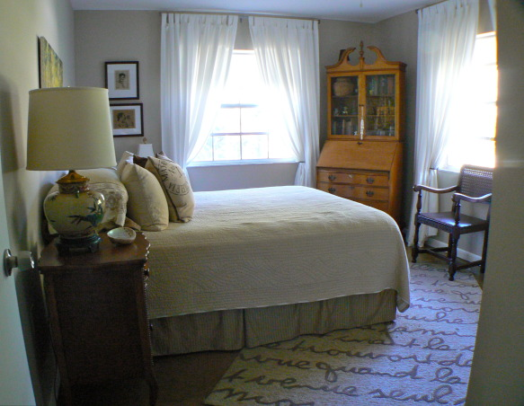 My Guest Bedroom, 11 x 12 Bedroom with Neutral colors, filled with antique furniture, original artwork, and estate sale finds. Refinished concrete floor with area rug. Two large windows with white cotton drapes for a bright, calming space. I am still looking for the perfect headboard, possibly upholstered., Calming neutral tones of brown and caramel. Antique drop front desk with drawer space for guests. Comfortable early 17th century arm chair. Estate sale find Oriental style bedside lamp on a birdseye maple nightstand. Area rug with french poem on refinished concrete floor. , Bedrooms   Design