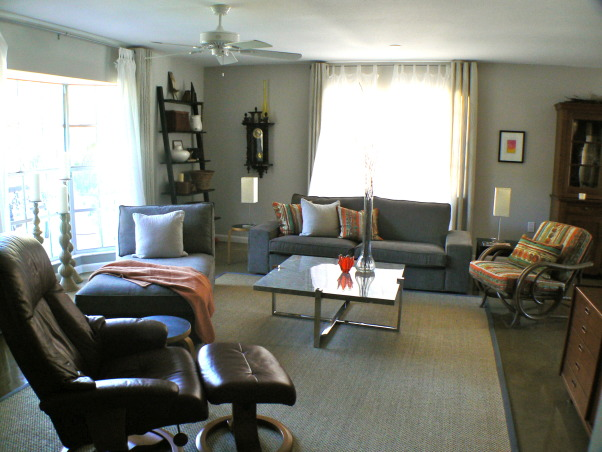 Change for the seasons, 15 x 19 Living/Family room area painted in Dove grey. Ikea sofa/sectional in grey-brown cordoroy covers, Classic slope arm chair, old wood bench/coffee table, teak end tables in separate styles, Stressless recliner. Blend of old and new . Refinished concrete floors with sisal area rug. Kids and cat friendly!, Sisal rug covers refinished concrete floor. Large windows with Ikea draperies and sheers. Leaning display shelves on either side of floor to ceiling bay window.    , Living Rooms    Design