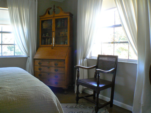 My Guest Bedroom, 11 x 12 Bedroom with Neutral colors, filled with antique furniture, original artwork, and estate sale finds. Refinished concrete floor with area rug. Two large windows with white cotton drapes for a bright, calming space. I am still looking for the perfect headboard, possibly upholstered., Antique drop down desk and 17th century arm chair amid large windows with white cotton drapery. , Bedrooms   Design