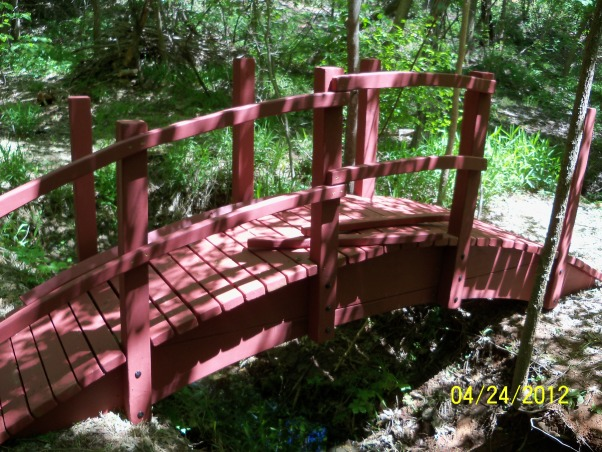 Oriental Arched Bridge, Deep in a prairie canyon runs a small stream beneath an earthen dam.  A singing flow of water splashes into a pool below the dam and continues its course along this winding stream.  On both sides of the stream long, narrow terraces, nestled beneath a dense canopy of oaks, willows, and elms, invite to be developed into a Japanese style retreat as refuge from the sweltering heat of a typical Oklahoma summer day.  The first order of course was the construction of a 12 foot span arched bridge complemented with an oriental pedestal lantern.  Some might think this an odd vision for a prairie environment.  I would suggest there is hardly a better design to enhance the scene.  , The final touch is assembling the railings.  I liked the double railing look best.  The right amount of curve was a challenge.  I couldn't get the right amount of curve from a 2x12x12' board so I segmented the rails to accomplish the effect.  , Patios & Decks Design