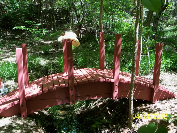 Oriental Arched Bridge, Deep in a prairie canyon runs a small stream beneath an earthen dam.  A singing flow of water splashes into a pool below the dam and continues its course along this winding stream.  On both sides of the stream long, narrow terraces, nestled beneath a dense canopy of oaks, willows, and elms, invite to be developed into a Japanese style retreat as refuge from the sweltering heat of a typical Oklahoma summer day.  The first order of course was the construction of a 12 foot span arched bridge complemented with an oriental pedestal lantern.  Some might think this an odd vision for a prairie environment.  I would suggest there is hardly a better design to enhance the scene.  , Cowboy hat optional. , Patios & Decks Design
