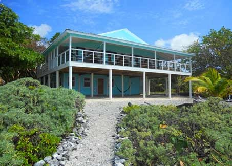 Utila Beach House with Long Living Room, I am enclosing a front porch to make a long living room (12'x 36'). I'm having problems figuring out what furniture to get and how to place it. There are three double doors opening onto the new front porch with a view of the ocean, which I want to take advantage of. Any suggestions would be greatly appreciated!, This is the front of the house after the new porch addition was completed. The photo was taken while standing on the beach, and the camera angle exaggerates the slope up the path. It is not as steep as it appears here. , Living Rooms Design