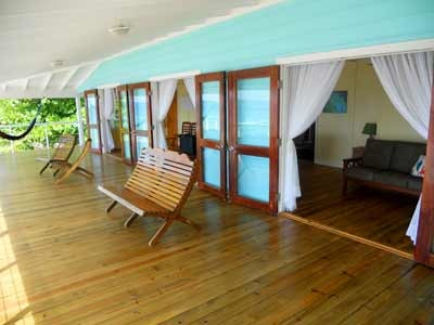 Utila Beach House with Long Living Room, I am enclosing a front porch to make a long living room (12'x 36'). I'm having problems figuring out what furniture to get and how to place it. There are three double doors opening onto the new front porch with a view of the ocean, which I want to take advantage of. Any suggestions would be greatly appreciated!, The new front porch has local Honduran tongue-and-groove wood floors. The handmade french doors are a different type of local Honduran wood, and were made on Utila by the local carpentry shop. They were reused from the original front of the house.  , Living Rooms Design