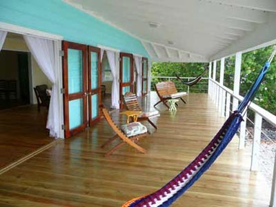 Utila Beach House with Long Living Room, I am enclosing a front porch to make a long living room (12'x 36'). I'm having problems figuring out what furniture to get and how to place it. There are three double doors opening onto the new front porch with a view of the ocean, which I want to take advantage of. Any suggestions would be greatly appreciated!, The new front porch has hammocks at each end. The 12 x 48 porch is actually an outdoor living room that overlooks the beach. The french doors open into the living room and allow excellent breezes throughout the house. , Living Rooms Design