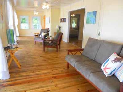 Utila Beach House with Long Living Room, I am enclosing a front porch to make a long living room (12'x 36'). I'm having problems figuring out what furniture to get and how to place it. There are three double doors opening onto the new front porch with a view of the ocean, which I want to take advantage of. Any suggestions would be greatly appreciated!, This angle shows the couch in front of one door, the two chairs in the center of the room, and a small grouping of chairs and the orange table at the far end. Rugs, coffee tables, a bar and a desk are all on the wish list. , Living Rooms Design