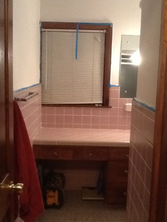 "Grey and Pink, Description: We have an L- shaped bathroom which we want to freshen up.We can't afford to replace tile or fixtures, basically want to paint,get new lighting,wall decor etc.There is grey tile from the floor to 55"" up the wall.There is also a matching grey tile counter that is 90"" long and has three drawers running horizontally and three drawers vertically with two sliding doors with shelving underneath.These are stained in a dark finish. I believe the wood is pine. There is also one window facing North which has the same dark stain as the drawers.This tile counter houses our pink sink.Above the sink is a large mirror which is 46"" long by 30"" tall. There is grey tile which borders the bottom edge of this mirror, so think we have to keep the mirror... But possibly build a frame around to update it? Our toilet is pink.There is also a small walk in shower with glass door.We have two hanging lights above sink which we want to replace.Our home is 55 years old and decorated pretty traditionally.I am at a loss as to how to update. My husband refuses to wallpaper this room again. I want to brighten it up, but need suggestions for a paint color.Also quite a bit of empty wall space which will need something on it.Also any ideas for new lighting? Should wood be painted ( drawers,cabinets, window?) Any ideas, suggestions will be greatly appreciated.Thank you., door view , Bathrooms Design"