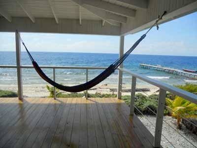 Utila Beach House with Long Living Room, I am enclosing a front porch to make a long living room (12'x 36'). I'm having problems figuring out what furniture to get and how to place it. There are three double doors opening onto the new front porch with a view of the ocean, which I want to take advantage of. Any suggestions would be greatly appreciated!, It's done!! The new front porch and living room are finished - except for the furnishings, which was the problem I originally posted about. The renovation ran a little over the estimate (don't they all?), so we will be adding more as the budget allows, but for now, we just enjoy the view. Thanks to everyone for some inspiring suggestions., Living Rooms Design