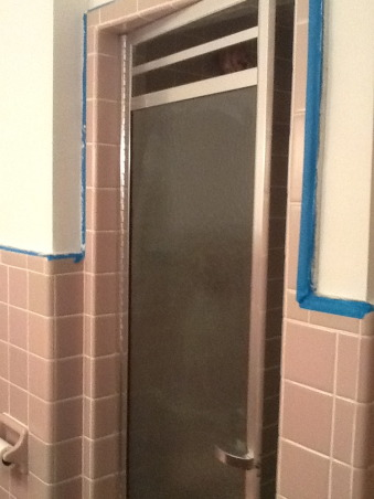 "Grey and Pink, Description: We have an L- shaped bathroom which we want to freshen up.We can't afford to replace tile or fixtures, basically want to paint,get new lighting,wall decor etc.There is grey tile from the floor to 55"" up the wall.There is also a matching grey tile counter that is 90"" long and has three drawers running horizontally and three drawers vertically with two sliding doors with shelving underneath.These are stained in a dark finish. I believe the wood is pine. There is also one window facing North which has the same dark stain as the drawers.This tile counter houses our pink sink.Above the sink is a large mirror which is 46"" long by 30"" tall. There is grey tile which borders the bottom edge of this mirror, so think we have to keep the mirror... But possibly build a frame around to update it? Our toilet is pink.There is also a small walk in shower with glass door.We have two hanging lights above sink which we want to replace.Our home is 55 years old and decorated pretty traditionally.I am at a loss as to how to update. My husband refuses to wallpaper this room again. I want to brighten it up, but need suggestions for a paint color.Also quite a bit of empty wall space which will need something on it.Also any ideas for new lighting? Should wood be painted ( drawers,cabinets, window?) Any ideas, suggestions will be greatly appreciated.Thank you., stand up shower , Bathrooms Design"