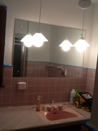 "Grey and Pink, Description: We have an L- shaped bathroom which we want to freshen up.We can't afford to replace tile or fixtures, basically want to paint,get new lighting,wall decor etc.There is grey tile from the floor to 55"" up the wall.There is also a matching grey tile counter that is 90"" long and has three drawers running horizontally and three drawers vertically with two sliding doors with shelving underneath.These are stained in a dark finish. I believe the wood is pine. There is also one window facing North which has the same dark stain as the drawers.This tile counter houses our pink sink.Above the sink is a large mirror which is 46"" long by 30"" tall. There is grey tile which borders the bottom edge of this mirror, so think we have to keep the mirror... But possibly build a frame around to update it? Our toilet is pink.There is also a small walk in shower with glass door.We have two hanging lights above sink which we want to replace.Our home is 55 years old and decorated pretty traditionally.I am at a loss as to how to update. My husband refuses to wallpaper this room again. I want to brighten it up, but need suggestions for a paint color.Also quite a bit of empty wall space which will need something on it.Also any ideas for new lighting? Should wood be painted ( drawers,cabinets, window?) Any ideas, suggestions will be greatly appreciated.Thank you., outdated mirror and lighting , Bathrooms Design"