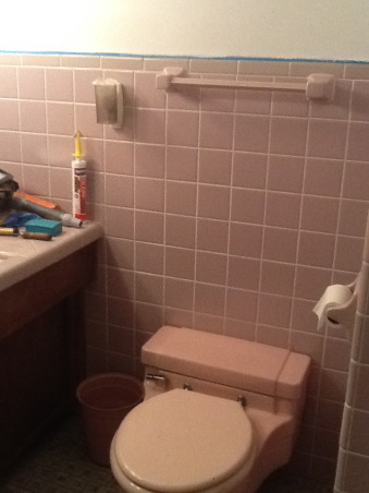 """Grey and Pink, Description: We have an L- shaped bathroom which we want to freshen up.We can't afford to replace tile or fixtures, basically want to paint,get new lighting,wall decor etc.There is grey tile from the floor to 55"""" up the wall.There is also a matching grey tile counter that is 90"""" long and has three drawers running horizontally and three drawers vertically with two sliding doors with shelving underneath.These are stained in a dark finish. I believe the wood is pine. There is also one window facing North which has the same dark stain as the drawers.This tile counter houses our pink sink.Above the sink is a large mirror which is 46"""" long by 30"""" tall. There is grey tile which borders the bottom edge of this mirror, so think we have to keep the mirror... But possibly build a frame around to update it? Our toilet is pink.There is also a small walk in shower with glass door.We have two hanging lights above sink which we want to replace.Our home is 55 years old and decorated pretty traditionally.I am at a loss as to how to update. My husband refuses to wallpaper this room again. I want to brighten it up, but need suggestions for a paint color.Also quite a bit of empty wall space which will need something on it.Also any ideas for new lighting? Should wood be painted ( drawers,cabinets, window?) Any ideas, suggestions will be greatly appreciated.Thank you., pink toilet , Bathrooms Design"""