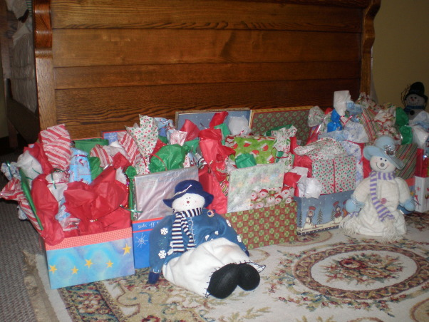 Christmas cheer, These are just few of my Christmas displays. My kids gave me the antique window for Christmas one year. The boxes full of little gifts are for the grandkids. I wrap each one, they love to open gifts, they are just one dollar items. A tradition my mom did. Thank goodness for the Dollar Tree and The Mighty Dollar.  I was so tickle when I found the book of The Littlest Snowman, it works well with these little fellows., These sit at the foot of my bed, not enough room under the tree. You can see these from the livingroom. We have a small home, but it works for us., Holidays Design