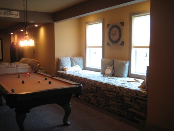 Warm and Cozy in a big space, We just recently finished our basement.  It was a very big and long space.  We wanted to create a warm, cabin like feeling and a space our soon to be teenage daughter could go to hang with friends., Large window seat overlooks wooded area, Basements Design