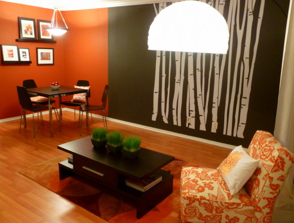 Orange and Gray Living Room, This is a rent apartment, so I can't make major changes. I would have change the ceiling lamp, but, oh well. The paint is a dark charcoal ( Behr DARK CAVERN), the other is orange (Behr KOI, but it was too bright so the helpful guys at Home Depot help me and they added more black so the color became a spice/terracota).  The coffee table is from OVERSTOCK, the carpet from HAYNEEDLE, table, chairs and floor lamp from IKEA, photo frames from WEST ELM, shelfs from CRATE & BARREL, orange print chair from TARGET, orange rectangular pillow from CHIASSO. , Living room. Right where the trees are, there should be a sofa (I'm still trying to find one).    , Living Rooms Design