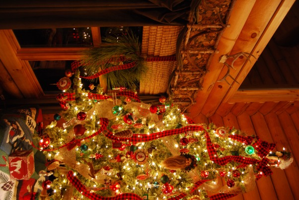 "Our Log Home Christmas 2012, It has been a few years since I have posted any pix of the interior decorations here at our log home deep in the secluded woods in the North Georgia Mountains. Thought I should get ""unlazy"" and post a few., Great room tree with burlap and buffalo plaid ribbons. Rather than having to put up and decorate a very tall tree, we opt to place an 8 foot tree on a card table draped with a beautiful plaid tablecloth to the floor. It serves the purpose, gives basically the same look as a tall tree would, but requires a LOT less lights and ornaments! A few extra large wrapped gift boxes placed on the floor surrounding the table do a good job of breaking up the draped tablecloth.            , Holidays Design"