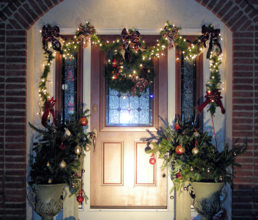 "Symmetric Curb Appeal Winter Holidays, Changing entryway to reflect the wintry charm of the holiday season., Pine boughs replaced the summer flowers shown in the previous post ""Symmetric Curb Appeal"".  The pine is covered with shatterproof ornaments in red and gold. The door swag and wreath are re-used every year. This is night photo with spotlight and small white lights.  , Home Exterior Design"