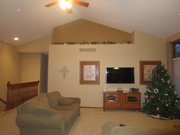 Great Room, I need help coming up with ideas for the main wall for our new house!   At its peak the ceiling is just over 14 feet tall -- TV was prewired -but off center.   Ideas for color?  What to do with accented space at the top?   I'm at a total loss!!  Ignore the tiny christmas tree -- its moving to the basement next year!!, I need help with this wall.  Unsure of what color to use for the accent space and what to put up there.   TV was prewired in place.  Just moved in and want to make the space more cozy.    *ignore the tree in the corner, its too small and will be moving to the game room in the basement next year.   Ceiling at its peak is about 14'.  wall in front is 9.5'.  opens to informal dining, kitchen and music room., Living Rooms Design