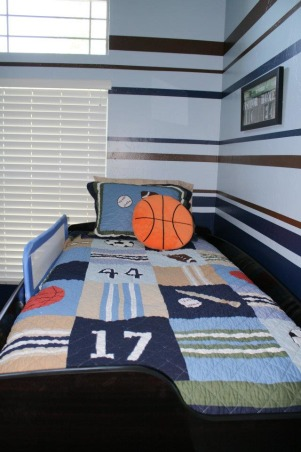 "Boys Brown/Blue Sports Room, This is my toddler's sports themed room.  It is a small, tall room and I had difficulty determining the best way to handle the walls.  I found another HGTV Rate my Space room that had the same bed spread and ""borrowed"" the paint stripes from that space.  I love feedback from people with more experience on how to improve so please don't hesitate to let me know if you have other / better ideas., This is a view from the foot of his bed. , Boys' Rooms Design"