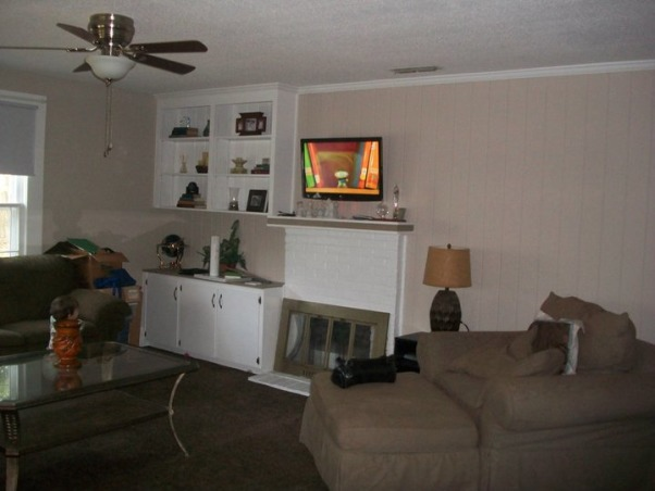 Living room trouble, I am in the midst of redecorating our living room. We are going with a coastal cottage vibe. I plan on painting the walls an almost white shade and using a hunter green (like the sofas), butter yellow and sky blue color palette to make it pop. My biggest problem is our wall with the fireplace. We have a built in to the left of the fireplace but just an open wall to the right, leaving the room very left side heavy. I would love to one day build a matching built in to the other side, but right now its not an option. I desperately need ideas for the right side of the fireplace and any suggestions on furniture placement. Just to help, we no longer have the coffee table or the lounge chair that is in the pictures, just the sofa and love seat., fireplace wall, view from front door , Living Rooms Design