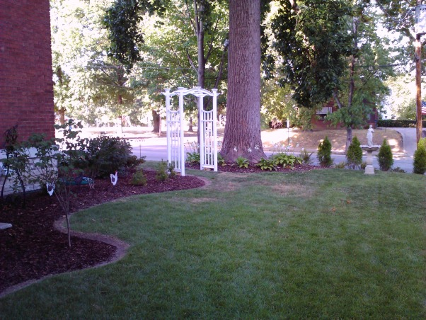 Historic 1855 Italianate in need of TLC, We bought this house two years ago and have been dividing our time between the inside of the house and the lawn and gardens.  I am the yard person in this family and since moving here I have hurt my foot and I really need help with ideas on what to do with the steep side-yard slope to avoid having to mow that area., I just added more beds around the house toward the sloped side-yard and we added a entry arbor to the back side of the yard.   Eventually the shrubs will grow large enough to be a living fence from the house to the arbor and then from around the tree to the back fence that we put up this past spring.       , Yards Design