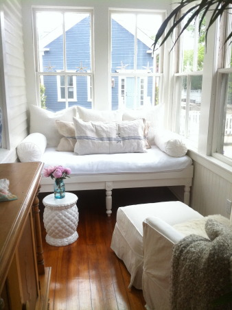 Cozy Cottage Porch Makeover, The porch of my Victorian cottage was enclosed back in the 20s.  I painted it white with a blue ceiling, refinished the hardwood floors, added a custom built daybed and lots of blue and white.  The shelving holds my ironstone and aqua mason jars and bottles, and seagrass baskets are used for storage.  A Dash and Albert outdoor rug withstands heavy traffic. The Starfish pillow is from local artist Willywaw.  Vintage french grain sacks are used as pillow cases. Since the porch is south facing it gets great sun and warms up enough in winter so we can use it year round!, The daybed - which we had built for the space since it's too narrow for a standard bed.  This is where I spend most mornings with coffee and evenings sipping wine.  I found vintage French grain sacks on eBay to use for pillow cases.   , Porches Design