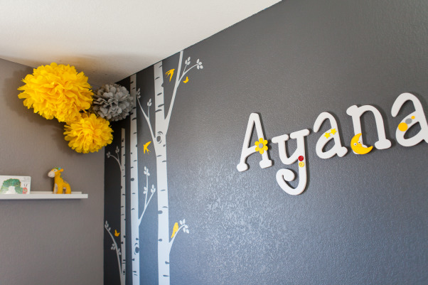 "Ayana's Sweet and Modern Nursery, I am a lover of contemporary living. Ever since I thought of making our daughter's nursery I was looking for something that looks modern and contemporary. After my rigorous research I finally settled down to ""Gray and Yellow"" theme, Gray was to give the room that elegance and Yellow was to diffuse that freshness and incandescence for a girl's room. I loved how the combination was vivid as well as graceful.  However, I wanted to keep a balance between splurging for the nursery and 'thinking too much'. I think I was able to get to it finally!  I got my inspiration from all the beautiful projects that have been submitted already. I had previously done my son's room, and I also wanted Ayana's room to be as pretty as she herself is.  Room Details- 1.	Wall Colors-  Behr (Twenty Carat, Cathedral Gray, and Manhattan Mist) 2.	Crib- Baby Mod 3.	Dresser- IKEA 4.	Changing Table- Pottery Barn 5.	Chair- American Furniture Warehouse 6.	Curtain- Bed Bath and Beyond 7.	Poms- Ebay 8.	Wall Decals- Etsy 9.	Birdhouse Lamp- DIY project 10.	Small Birdhouse- DIY project 11.	Door name tag- DIY Project 12.	Wall name letters-  I bought wooden letters off of Etsy and then painted and decorated them so it was partial DIY project. 13.	Wall shelf- IKEA 14.	Round Mirrors- Target 15.	Butterfly Mirror- Michaels 16.	Nursery Art- Gift from a friend 17.	Yellow Lamp- IKEA  **Thanks to my husband AJ Kumar for taking wonderful shots of the nursery!, Nurseries Design"
