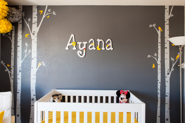 "Ayana's Sweet and Modern Nursery, I am a lover of contemporary living. Ever since I thought of making our daughter's nursery I was looking for something that looks modern and contemporary. After my rigorous research I finally settled down to ""Gray and Yellow"" theme, Gray was to give the room that elegance and Yellow was to diffuse that freshness and incandescence for a girl's room. I loved how the combination was vivid as well as graceful.  However, I wanted to keep a balance between splurging for the nursery and 'thinking too much'. I think I was able to get to it finally!  I got my inspiration from all the beautiful projects that have been submitted already. I had previously done my son's room, and I also wanted Ayana's room to be as pretty as she herself is.  Room Details- 1.	Wall Colors-  Behr (Twenty Carat, Cathedral Gray, and Manhattan Mist) 2.	Crib- Baby Mod 3.	Dresser- IKEA 4.	Changing Table- Pottery Barn 5.	Chair- American Furniture Warehouse 6.	Curtain- Bed Bath and Beyond 7.	Poms- Ebay 8.	Wall Decals- Etsy 9.	Birdhouse Lamp- DIY project 10.	Small Birdhouse- DIY project 11.	Door name tag- DIY Project 12.	Wall name letters-  I bought wooden letters off of Etsy and then painted and decorated them so it was partial DIY project. 13.	Wall shelf- IKEA 14.	Round Mirrors- Target 15.	Butterfly Mirror- Michaels 16.	Nursery Art- Gift from a friend 17.	Yellow Lamp- IKEA  **Thanks to my husband AJ Kumar for taking wonderful shots of the nursery!, I enjoyed painting and decorating the name letters. It was an interesting task to pick different decoration piece for each letter. I wanted to keep it simple yet stylish as well as not to stray from the theme of the room.    , Nurseries Design"