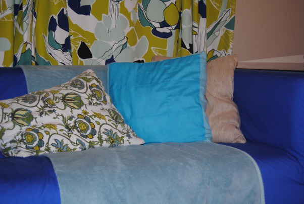 IKEA + me Family Room, Yes, I love color. Yes, I love IKEA. This room showcases both. I would--of course--love any positive feedback on my space, but also let me know if you have suggestions for small improvements. Thanks!, More pillows! The patterned pillow features a slipcover I made out of four fabric place mats I purchased at Dollar Tree--my favorite dollar store. The blanket breaks up the bright blue of the couch, but its real purpose is to mask the remnants of my son's handiwork--he got a hold of some royal-blue paint and poured it onto the couch. , Living Rooms Design