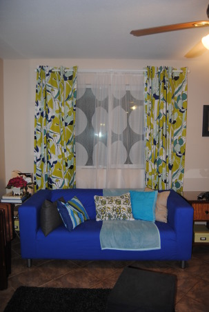 IKEA + me Family Room, Yes, I love color. Yes, I love IKEA. This room showcases both. I would--of course--love any positive feedback on my space, but also let me know if you have suggestions for small improvements. Thanks!, A view of our front window with the drapes open. Both sets of drapes are from IKEA, and the blue and green ones more or less directed the rest of the room. My husband insisted on having a second layer for privacy, and I love this choice because it is graphic, lightweight, and lets in lots of light and preserves some visibility. , Living Rooms Design