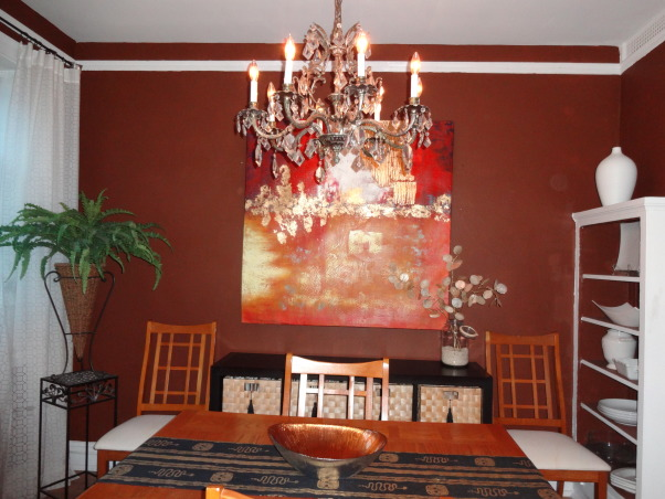 "Yummy Dining Room, Though the dining room is small it packs some big punch!  I painted the room chocolate truffle and the molding vanilla ice cream.  The crystal chandelier I inherited. (I had it rewired.)  I refurbished the chandelier with a lot of TLC and elbow grease.  I made the runner.  The ""buffet"" is actually a bookshelf on it's side with basket drawers.  I added the tassels.  My everyday plates, bowls, and coffee cups are within easy reach.  The framed letter is one that was found when my father was in WWII written to my aunts.  A definite treasure!, Chocolate Truffle paint on the  with Vanilla Ice on the moldings.  Chandelier was inherited and refurbished with a lot of TLC and elbow grease. The table runner is custom (I made.) The buffet is actually a book case on it's side with basket drawers.  I added the tassels, Dining Rooms Design"