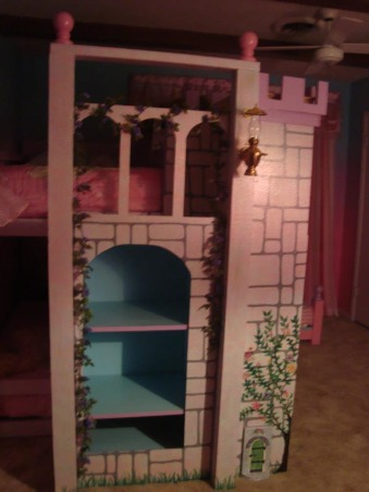 Princess room for three, We lost our son and daughter in law in Oct. 2012 and found we would be sharing in the raising of our three grand-daughters. We wanted them to feel overwhelming love and have a magical place to just be little girls and let their imagination run free. The castle was born! We created this room with mostly recycled furniture and some wood and about 5 gallons of paint. We think it came out beautiful. Three tone walls, custom bed, and darling chandelier, make this room a magical spot in our home. , Side of castle has three display shelfs and a balcony. , Girls' Rooms Design