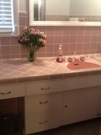 "Grey and Pink, Description: We have an L- shaped bathroom which we want to freshen up.We can't afford to replace tile or fixtures, basically want to paint,get new lighting,wall decor etc.There is grey tile from the floor to 55"" up the wall.There is also a matching grey tile counter that is 90"" long and has three drawers running horizontally and three drawers vertically with two sliding doors with shelving underneath.These are stained in a dark finish. I believe the wood is pine. There is also one window facing North which has the same dark stain as the drawers.This tile counter houses our pink sink.Above the sink is a large mirror which is 46"" long by 30"" tall. There is grey tile which borders the bottom edge of this mirror, so think we have to keep the mirror... But possibly build a frame around to update it? Our toilet is pink.There is also a small walk in shower with glass door.We have two hanging lights above sink which we want to replace.Our home is 55 years old and decorated pretty traditionally.I am at a loss as to how to update. My husband refuses to wallpaper this room again. I want to brighten it up, but need suggestions for a paint color.Also quite a bit of empty wall space which will need something on it.Also any ideas for new lighting? Should wood be painted ( drawers,cabinets, window?) Any ideas, suggestions will be greatly appreciated.Thank you., after (cabinets), Bathrooms Design"