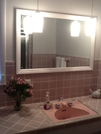 "Grey and Pink, Description: We have an L- shaped bathroom which we want to freshen up.We can't afford to replace tile or fixtures, basically want to paint,get new lighting,wall decor etc.There is grey tile from the floor to 55"" up the wall.There is also a matching grey tile counter that is 90"" long and has three drawers running horizontally and three drawers vertically with two sliding doors with shelving underneath.These are stained in a dark finish. I believe the wood is pine. There is also one window facing North which has the same dark stain as the drawers.This tile counter houses our pink sink.Above the sink is a large mirror which is 46"" long by 30"" tall. There is grey tile which borders the bottom edge of this mirror, so think we have to keep the mirror... But possibly build a frame around to update it? Our toilet is pink.There is also a small walk in shower with glass door.We have two hanging lights above sink which we want to replace.Our home is 55 years old and decorated pretty traditionally.I am at a loss as to how to update. My husband refuses to wallpaper this room again. I want to brighten it up, but need suggestions for a paint color.Also quite a bit of empty wall space which will need something on it.Also any ideas for new lighting? Should wood be painted ( drawers,cabinets, window?) Any ideas, suggestions will be greatly appreciated.Thank you., after (mirror and lighting), Bathrooms Design"