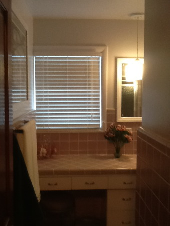 """Grey and Pink, Description: We have an L- shaped bathroom which we want to freshen up.We can't afford to replace tile or fixtures, basically want to paint,get new lighting,wall decor etc.There is grey tile from the floor to 55"""" up the wall.There is also a matching grey tile counter that is 90"""" long and has three drawers running horizontally and three drawers vertically with two sliding doors with shelving underneath.These are stained in a dark finish. I believe the wood is pine. There is also one window facing North which has the same dark stain as the drawers.This tile counter houses our pink sink.Above the sink is a large mirror which is 46"""" long by 30"""" tall. There is grey tile which borders the bottom edge of this mirror, so think we have to keep the mirror... But possibly build a frame around to update it? Our toilet is pink.There is also a small walk in shower with glass door.We have two hanging lights above sink which we want to replace.Our home is 55 years old and decorated pretty traditionally.I am at a loss as to how to update. My husband refuses to wallpaper this room again. I want to brighten it up, but need suggestions for a paint color.Also quite a bit of empty wall space which will need something on it.Also any ideas for new lighting? Should wood be painted ( drawers,cabinets, window?) Any ideas, suggestions will be greatly appreciated.Thank you., after (door view), Bathrooms Design"""