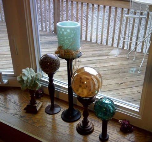 Beach Inspired Beige Living Room, Reinvented living room space from dark builders beige to a lighter creamier grey/beige in order to give a lighter airier beach feel. Added bamboo Roman Shade and Ocean colored sheers to large picture window. Beach glass colored accents add to the beach vibe. Hand painted crab pillow and the sand and shell tic-tac-toe art for a little whimsical fun., Picture window  Display with coral,glass ball filled with sand and shells, x-mas ball ornament covered with fishnet all glued to thrift store candle holders. and Yes! My front yard is a lake and not the beach.  , Living Rooms Design