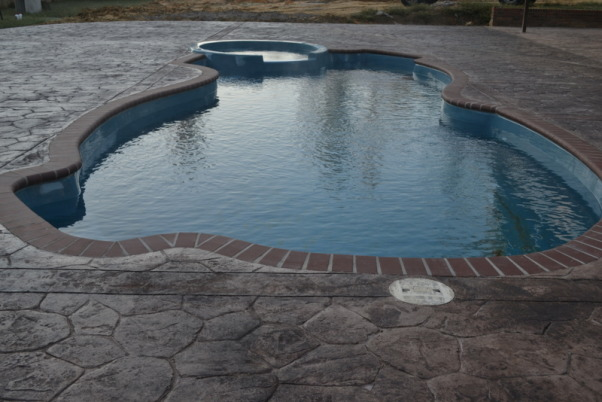 Waiting on Summer, Our pool project was completed after labor day so we didn't really get to use it this year. This is a fiberglass pool with brick surround and stamped concrete. The pool house is 18' x 30' including the porch and has vinyl cedar shake siding. It has a cathedral ceiling, 2 piece bath, kitchenette and an outside shower. The pool equipment is also in a separate room on the back. The floor in the pool house is also stamped concrete. There are about 25 yards of stamped concrete in this project. Due to the slope of the yard we excavated and had a retaining wall installed using the same brick that is on our house foundation. All of this is surrounded by a 6' privacy fence. Since it was late in the year we seeded with winter rye but had Bermuda sod installed beside the pool house. We plan on landscaping in the spring.  , Closer pic of stamped concrete and pool , Pools Design